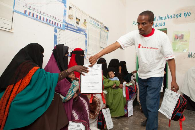 Jama Mohamed, Save the Children health programme manager for Save the Children, provides hygiene promotion kits to mothers at Hingod health post in Gardo, Puntland. Photo Colin Crowley/Save the Children
